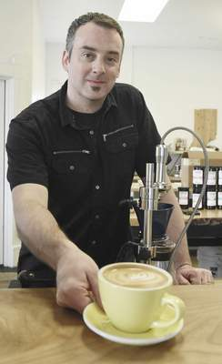 Michelle Davies | The Journal Gazette Corey Waldron, owner of Conjure Coffee, with a latte he made using the unique equipment he designed for his coffee shop.
