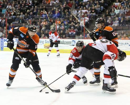 Tony Bailey Photography  Komets defensmen Curtis Leonard, left, and Bobby Shea, right, battle with Cincinnati Cyclones Justin Vaive, front right, and Justin Danforth, for the puck at U.S. Bank Arena on Saturday night in Cincinnati.