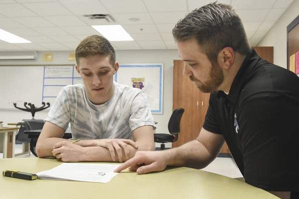 Michelle Davies | The Journal Gazette  Ryan Roy, department chair of special education at Carroll High School, works with Joe Just, senior, on strategies for reading comprehension.