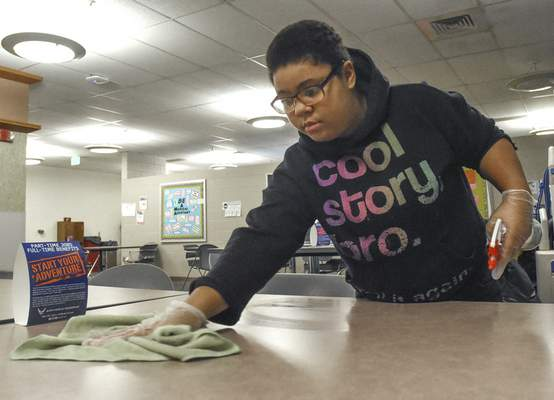 Wayne senior Adrianna Malone wipes down tables recently in the lounge at Ivy Tech's Coliseum Campus.