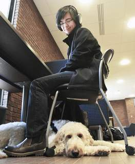 Cathie Rowand | The Journal Gazette Theo Thompson, a student at IPFW who is on the autism spectrum, has Sam, his service dog, to help keep him calm. (The_Journal_Gazette)