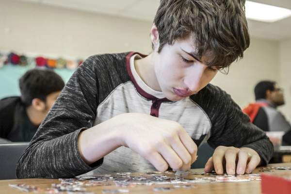 Mike Moore | The Journal Gazette Wayne freshman Griffin Baldus pieces together an Avengers puzzle Thursday. The Arc of Indiana awarded Wayne with its 2017 Education Impact Award for its special education work.