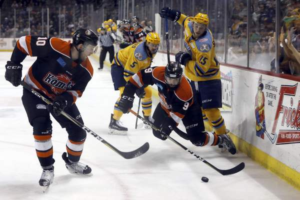 Katie Rausch   The Toledo Blade  Toledo's Austen Brassard, top, and Dylan Sadowy, right, can't get control of the puck from the Komets' Mason Baptista, middle,as he kicks it out to teammate Curtis Leonard, bottom, in the third period Saturday at the Huntington Center in Toledo, Ohio.