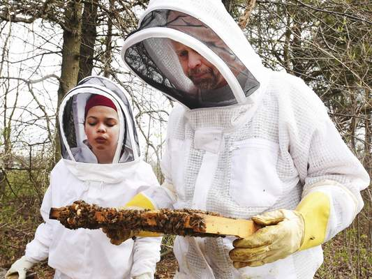 Photos by Cathie Rowand | The Journal Gazette Chris LaSalle and his daughter Samantha check for brood activity to see how well a beehive wintered.