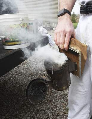 LaSalle prepares the smoker before checking his  beehives. Pouring smoke over the hives helps keep the bees calm.