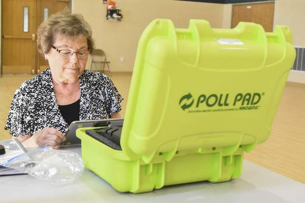 Jeanne Nicolet, inspector for the voting station at Good Shepherd United Methodist Church in St. Joseph Township, uses a Poll Pad to make sure all early votes have been recorded to ensure that no one votes twice. (Michelle Davies | The Journal Gazette)