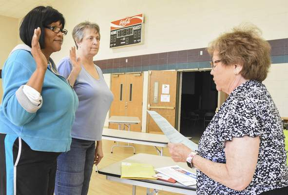 Michelle Davies | The Journal Gazette Jeanne Nicolet swears in Caroline Kinzer, right, Republican judge, and Amy Eisom, left, Democratic judge, Monday evening before setting up the polling booths for today's elections.