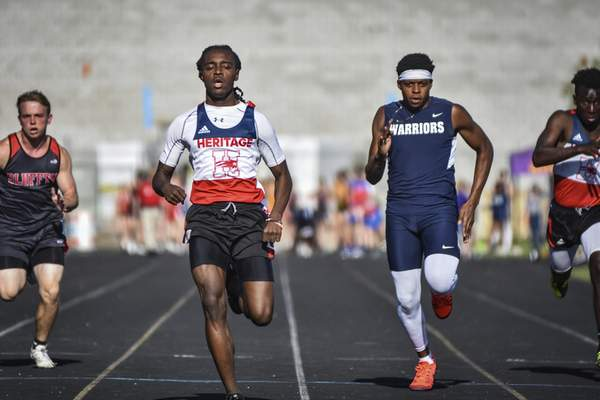 Mike Moore | The Journal Gazette  Heritage senior Hannibal Hall, center left, and Woodlan senior Ah'Lan Howard, right, compete in the 100-meter sprint during the ACAC Track and Field championships at New Haven on Tuesday.