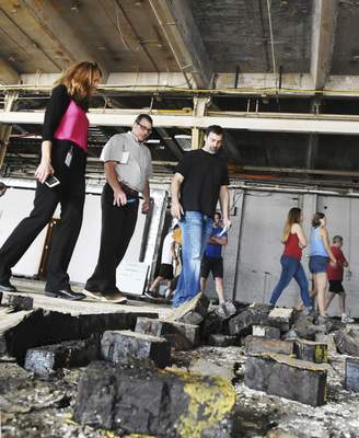Cathie Rowand | The Journal Gazette  People walk around a broken up wooden brick floor while touring Building 20, which could be a future restaurant, at the Electric Works campus Tuesday. Tours are at 10:30 a.m. Tuesdays and 4:30 p.m. Wednesdays throughout May and cover the first phase of the project on the former General Electric plant's west campus. People are encouraged to sign up online ahead of time at FortWayneElectricWorks.com.