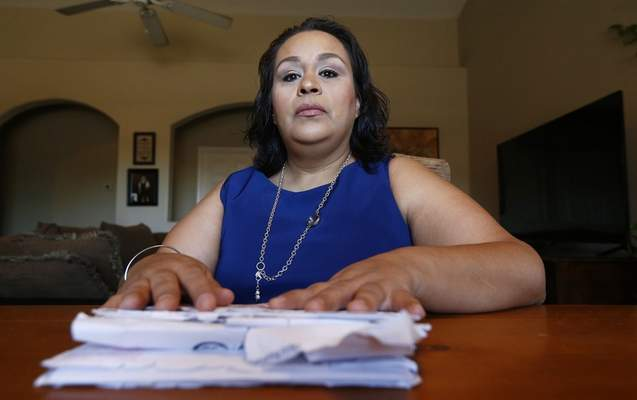 Associated Press  Josephine Rizo sits in her Phoenix home with her stack of bills from her ongoing battle with cancer. Rizo says the bills have forced her to basically restart her life.