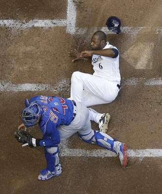 Associated Press Brewers outfielder Lorenzo Cain slides safely into home plate in front of Cubs catcher Willson Contreras during Tuesday's game in Milwaukee.