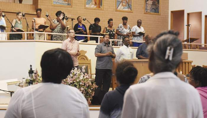 Pastor Raymond C. Dix Jr., center, sings with others during a community prayer service at Pilgrim Baptist Church on Gay Street. The gathering will be followed by weekly prayer walks. (Photos by Rachel Von | The Journal Gazette)