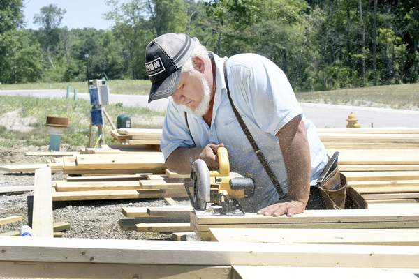Rachel Von | The Journal Gazette Wilbur Lengacher cuts wood for a house under construction on Carrara Court in Fort Wayne. New-home buyers could see a $9,000 jump in price because of tariffs on Canadian lumber.