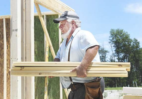 Rachel Von | The Journal Gazette  Wilbur Lengacher carries wood during the building of a house on Carrara Ct. in Fort Wayne, IN on Friday July 6, 2018. Home construction is one industry being effected locally by trade tariffs being imposed by the Trump Administration because it uses a lot of lumber from Canada.