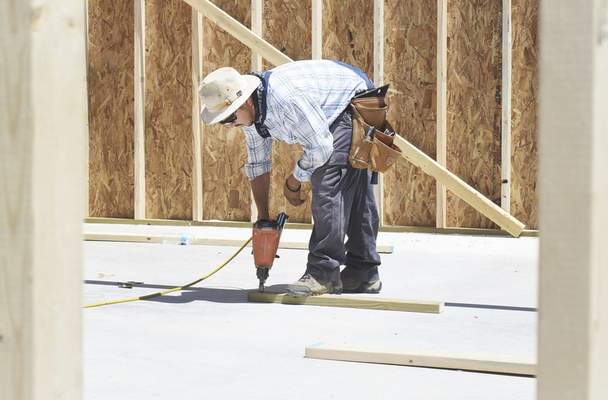 Rachel Von | The Journal Gazette  Damian Delgado works on a house being built on Carrara Ct. in Fort Wayne, IN on Friday July 6, 2018. Home construction is one industry being effected locally by trade tariffs being imposed by the Trump Administration because it uses a lot of lumber from Canada.