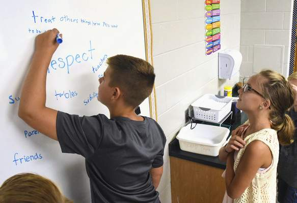 "Bret Sauder, a fourth-grader at Leo Elementary School, writes  what he thinks ""respect"" means on a dry-erase board while classmate Jensen Zeisloft waits her turn Tuesday afternoon."