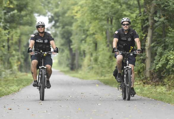 Michelle Davies | The Journal Gazette Fort Wayne Police Department bike patrol Officers Erik Melia, left, and Jason Crowder ride along the newly opened section of the Pufferbelly Trail on Monday afternoon.