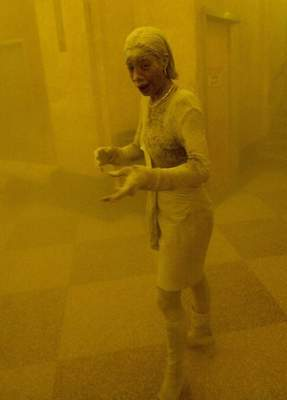 A woman covered in dust takes refuge in an office building after the top of one of the World Trade Center towers collapsed. The woman was caught outside on the street as the cloud of smoke and dust enveloped the area.