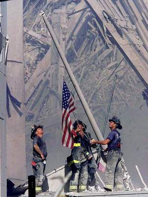 Associated Press: Brooklyn firefighters George Johnson, left, Dan McWilliams, center, and Billy Eisengrein raise a flag at the World Trade Center in New York.