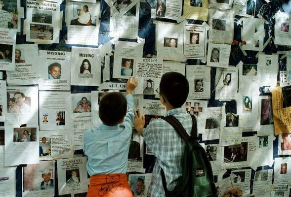 Washington Post: Two boys adjust a poster placed on a wall at Bellevue Hospital in New York, where families came to speak with officials about identifying their loved ones, dead or alive.