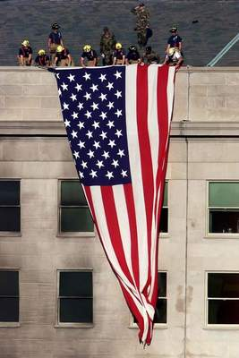 Washington Post: Firefighters along with a few military personnel on Sept. 12, 2001, drape a large flag over the west wall of the Pentagon a few yards from the area damaged by the attack the day before.