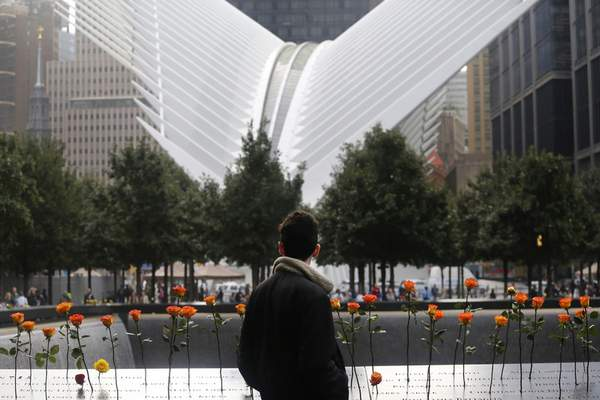 Associated Press photos A visitor stands at the World Trade Center memorial plaza in New York during a ceremony Tuesday on the anniversary of the 9/11 terrorist attacks.