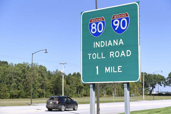 Ben Mikesell | The Journal Gazette Cars drive past a sign for the Indiana Toll Road Friday morning on C.R. 17 near Elkhart.