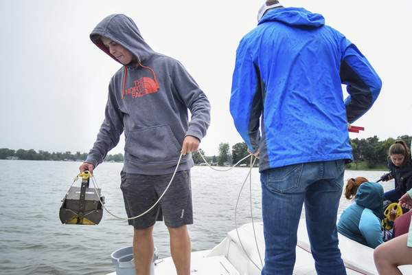 Students prepare to drop an Ekman Dredge, a device to grab samples from the depths of Winona Lake, which results in ...