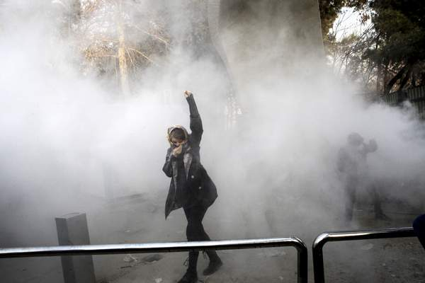 FILE-- In this Dec. 30, 2017 file photo, taken by an individual not employed by the Associated Press and obtained by the AP outside Iran, a university student attends a protest inside Tehran University while a smoke grenade is thrown by anti-riot Iranian police, in Tehran, Iran. (AP Photo, File)