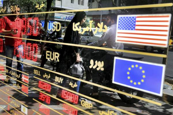 FILE - In this Wednesday, Sept. 5, 2018 file photo, various currency rates are displayed at a window of an exchange shop in downtown Tehran, Iran. (AP Photo/Ebrahim Noroozi, File)
