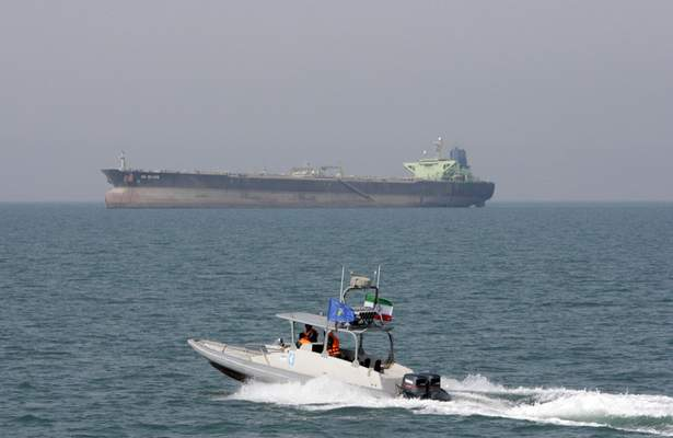 FILE-- In this July 2, 2012 file photo, an Iranian Revolutionary Guard speedboat moves in the Persian Gulf while an oil tanker is seen in background. (AP Photo/Vahid Salemi, File)