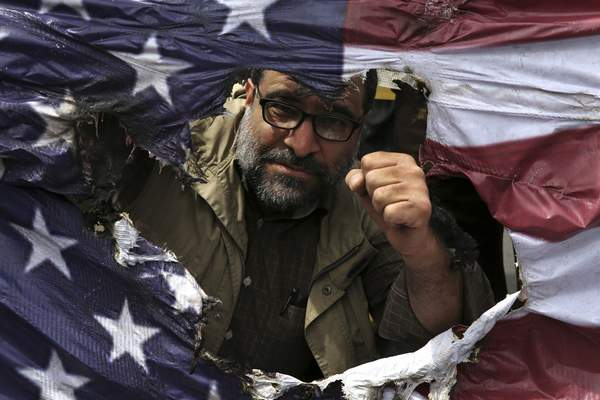 FILE - In this May 11, 2018 file photo, an Iranian protestor clenches his fist behind a burnt representation of the U.S. flag during a protest over U.S. President Donald Trump's decision to pull out of the nuclear deal with world powers, in Tehran, Iran. (AP Photo/Vahid Salemi, File)