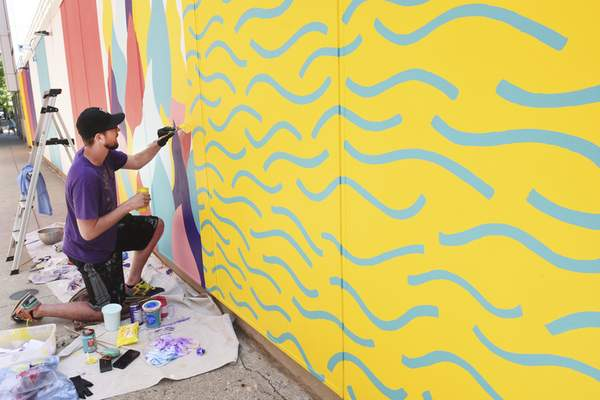 """File Matt Plett works on his """"Breathe"""" mural, which is one of the three Art This Way projects completed downtown this year."""