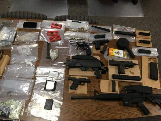 Courtesy Fort Wayne Police Department This photo shows drugs and guns seized by police Thursday evening at 3812 Trace Way. Police were called to the area on reports of shots fired and found the house had been riddled with bullet holes. Four people were taken into custody.