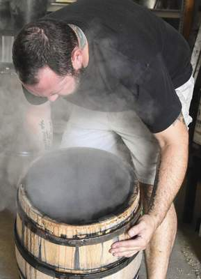Michelle Davies | The Journal Gazette Lipsky checks the level of charring of one of his barrels. If a barrel is too charred, it becomes useless and must be thrown out.