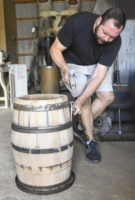 Michelle Davies | The Journal Gazette Matt Lipsky pounds on trussing hoops to make sure they are tight as he makes a whiskey barrel in his Fort Wayne shop.
