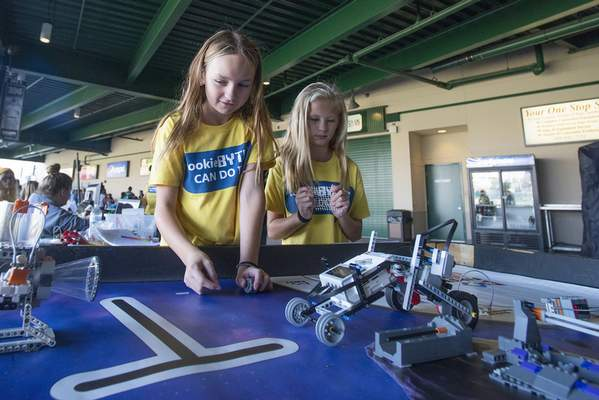 Brett Luke   The Journal Gazette  Kayla Meyer, 10, left, and Marley Willcox, 10, work together to solve tasks through the use of robotics and Legos at this year's Discover Girl Scouting eventat Parkview Field Sunday afternoon.