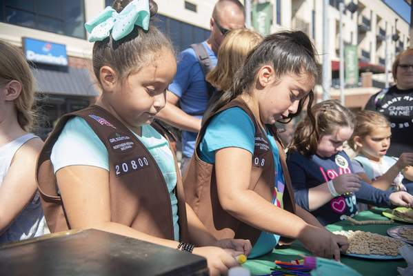 Brett Luke   The Journal Gazette  Esmeralda Nino, left, and her sister Isabella work to put bird feeders together Sunday at this year'sDiscover Girl Scoutingevent held at Parkview Field.