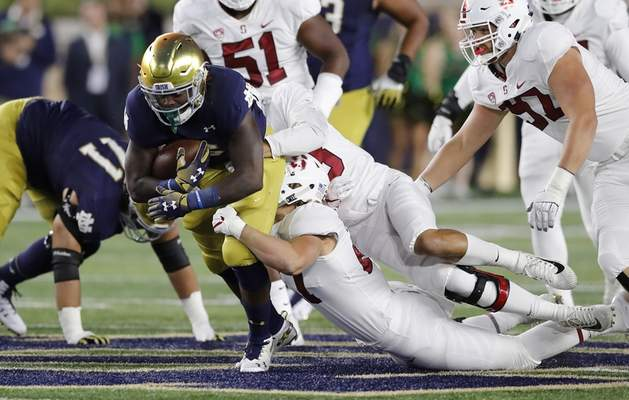 Notre Dame running back Tony Jones Jr. is stopped by the Stanford defense during the first half Saturday. Jones later left the game with an ankle injury. Coach Brian Kelly said he's likely to play against Virginia Tech. (AP Photo/Carlos Osorio)