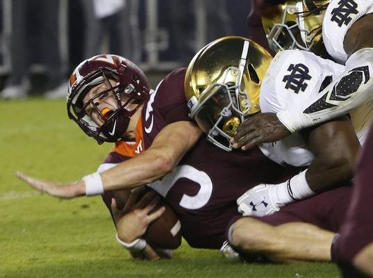 Virginia Tech quarterback Ryan Willis (5) is slammed to the ground by a group of Notre Dame tacklers on third down near the goal line during the first half in Blacksburg, Va., Saturday. (AP Photo/Steve Helber)