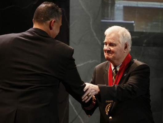 FILE - In this Nov. 21, 2010, file photo, former Kansas State basketball coach Tex Winter, right, shakes hands with Kansas State coach Frank Martin during the former's induction into the National Collegiate Basketball Hall of Fame in Kansas City, Mo. Winter, the innovative Triangle Offense pioneer who assisted Phil Jackson on 11 NBA championship teams with the Chicago Bulls and the Los Angeles Lakers, has died. He was 96. Kansas State University said Winter died Wednesday, Oct. 10, 2018, in Manhattan, Kan. (AP Photo/Ed Zurga, File)