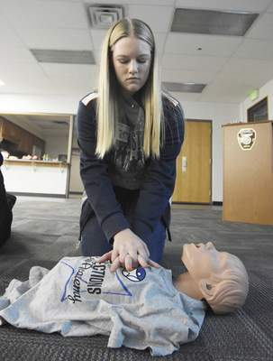 Rachel Von | The Journal Gazette Indiana Connections Career Academy student Hannah Boutwell, 14, works on practicing chest compressions during a CPR training session Friday led by Justin Foust, a student intern with Indiana Connections Career Academy who works at the fire station at Southwest Fire District Station 1 on Old Trail Road.