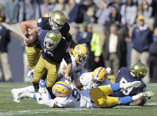 Notre Dame quarterback Ian Book is tackled by Pittsburgh linebacker Saleem Brightwell (9) is during the first half of an NCAA college football game, Saturday, Oct. 13, 2018, in South Bend, Ind. (AP Photo/Darron Cummings)