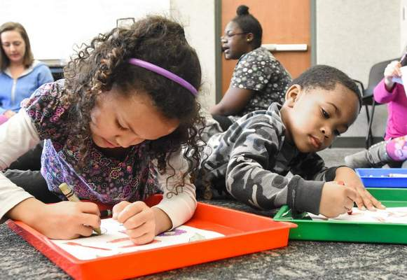 FILE: Jocelyn Byers, left, and Chase Jackson enjoy a moment of coloring after dancing, singing and playing during Learn and Grow Child Care at the Allen County Public Library's Waynedale branch.