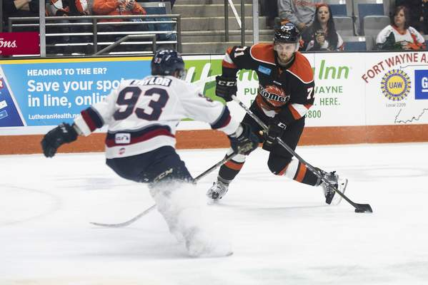 Brett Luke | The Journal Gazette  Ryan Lowney of the Komets takes a shot past Justin Taylor of Kalamazoo during the second period at the Coliseum on Saturday.