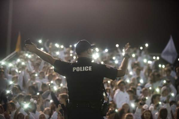 Fort Wayne Police Officer C. Fairchild  leads the Bishop Dwenger student section in song during halftime at the Fred Zollner Memorial Stadium this month. Fairchild was working security at the football game against Snider High School and is a familiar face at the school. (Brett Luke | The Journal Gazette)