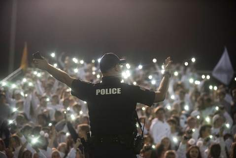 Fort Wayne Police Officer C. Fairchild  leads the Bishop Dwenger student section in song during halftime at the Fred Zollner Memorial Stadium this month. Fairchild was working security at the football game against Snider High School and is a familiar face at the school. (Brett Luke | The Journal Gazette) (Brett LukePhotographer)