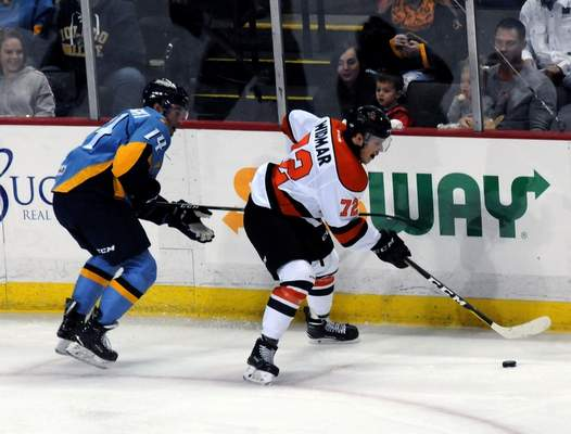 Justin A. Cohn   The Journal Gazette  Komets forward Joseph Widmar, right, looks to pass the puck in the offensive zone Saturday night at the Huntington Center as he's chased by the Toledo Walleye's Ryan Obuchowski in Toledo, Ohio.