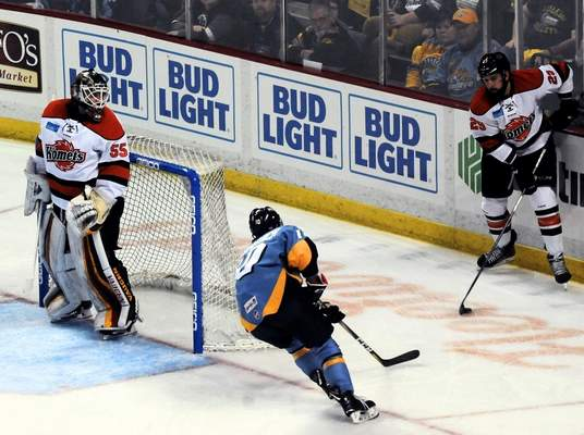 Justin A. Cohn   The Journal Gazette  Komets defenseman Chris Rygus, right, tries to move the puck out of trouble Saturday night as he's attacked by the Toledo Walleye's Shane Berschbach at the Huntington Center, as goaltender Lukas Hafner, left, looks on in Toledo, Ohio.