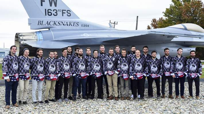 Mike Moore | The Journal Gazette The Fort Wayne Komets hockey team pose for a group photo in front of an F-16 Eagle in their new Blacksnake jerseys after a press conference at Heritage Park on Tuesday.